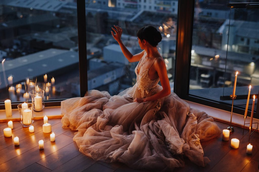 Bride wearing vaganbond bridal wedding dress surrounded by candles at dusk with a view of London